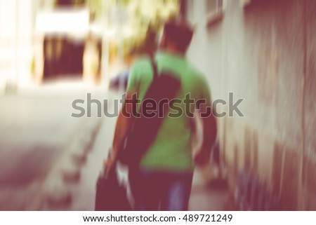 Blurry picture of man walking down the street