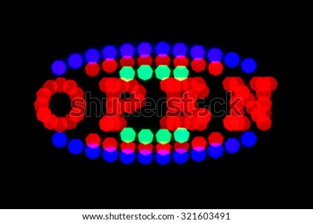 blurry red green and blue neon signboard with word open on black background - stock photo