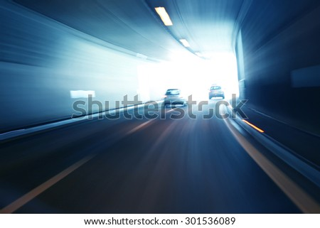 Blurry silver blue color tunnel high speed car driving. Motion blur visualizes the speed and dynamics. - stock photo