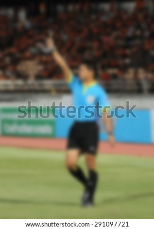 blurry Soccer referee holding yellow card for a soccer player. - stock photo