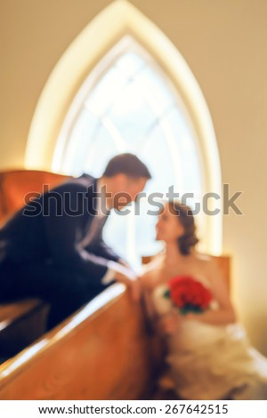 Blurry, soft, out of focus closeup portrait of smiling kissing young married couple, wedding day in church, blurry background