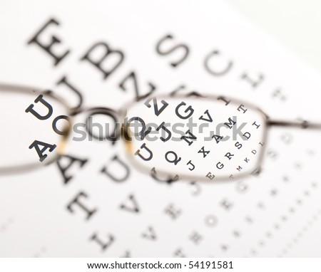Blurry text clearing up through eyeglass - medical optics concept - stock photo