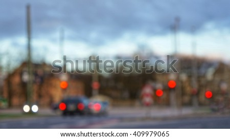 Blurry un-focused abstract scene of an intersection with few cars and traffic lights. Cloudy sky in the evening above. - stock photo
