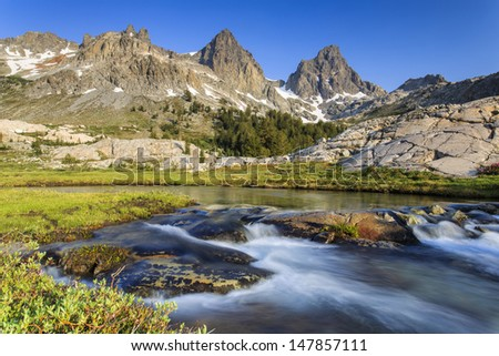 Blurry water flowing with the Sierra mountain range in the background - stock photo