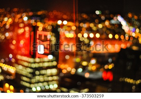Blury night city lights from lookout tower in Vancouver Canada with exit sign reflection - stock photo