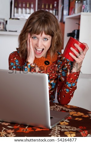 Blushing brunette with laptop holding red mug at a cafe - stock photo