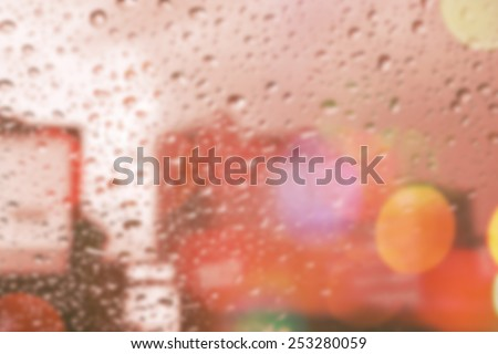 bluured of raindrops on window at night in the city - stock photo