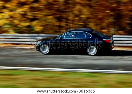 BMW at fast ride in the autumn. - stock photo