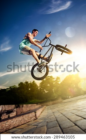bmx bicycle rider tricking on the highlights - stock photo
