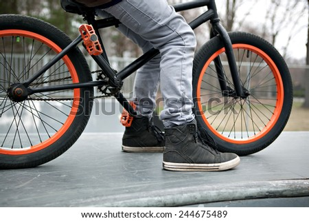 BMX bike rider parked atop a ramp at the skate park. - stock photo