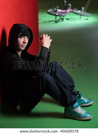 BMX biker - biker sitting on the floor, his bike is in the background (focus on the biker, the bike is out of DOF) - stock photo