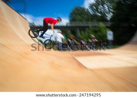 BMX Biker Performing Tricks during ride on a ramp - stock photo