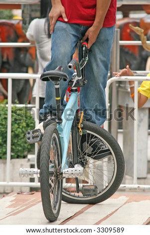 BMX biker performs a trick on the front wheel - stock photo