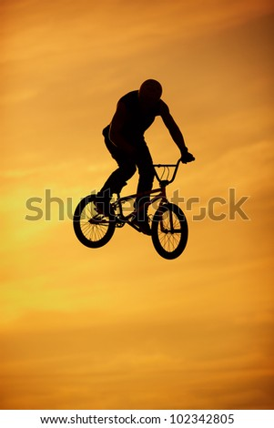 bmx jump on bright orange sky background - stock photo