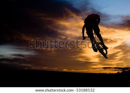 bmx rider at jump against sky at sundown - stock photo