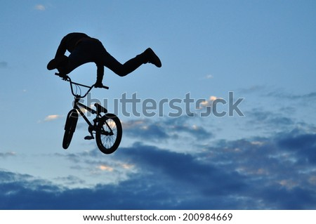 BMX rider making a bike jump - stock photo