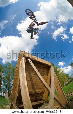 "BMX rider performing air trick ""tail-whip"" - stock photo"