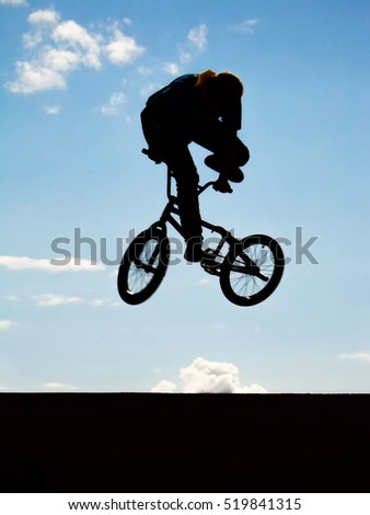 BMX rider performing air trick with clouds at the background