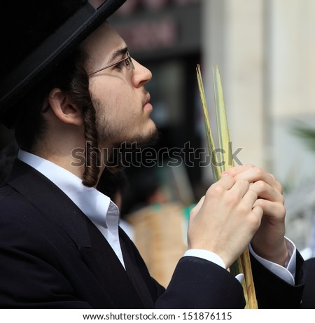 BNEI-BRAK, ISRAEL - SEPTEMBER 22: A young Orthodox Jew with side curls and black hat chooses ritual items Lula before the holiday of Sukkot September 22, 2010 in Bnei Brak, Israel - stock photo