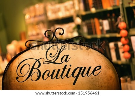 "Board at the store in antique style with the word ""boutique"""