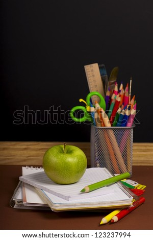 board, books, pencils, opened empty notebook lie on school desk
