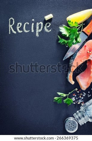 board for recipe and raw fish on a table - stock photo