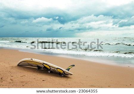 Board for windsurfing on the beach and cloudy sky - stock photo