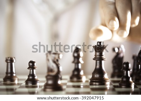 Board game, chess player hand about to play, excellence concept.