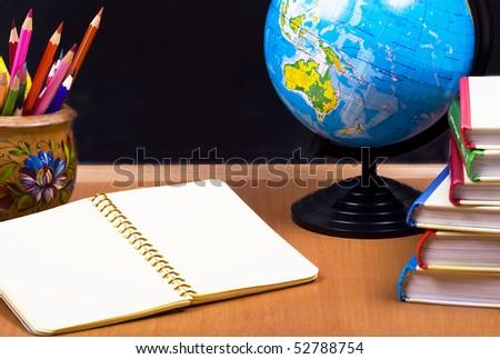 board, globe, books,  pencils, opened empty notebook lie on school desk - stock photo