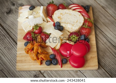 board of assorted cheese on weathered wooden table - stock photo