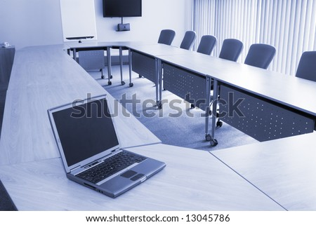 Board room in office block with laptop - stock photo