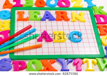 board with colorful magnetic letters that spell Learn abc - stock photo