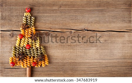 Board with natural decorations on wooden background. Set of different varieties of pasta in the form of a tree. Winter holidays concept