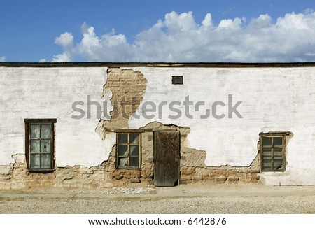 Boarded and abandoned adobe building with a door and windows. - stock photo