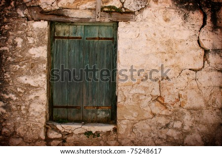 Boarded up green door and window of old cottage in Karia Lefkas Greece - stock photo