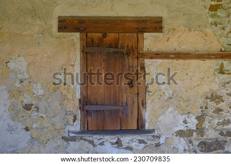 Boarded up old window on a brick and plaster old barn in need of restoration - stock photo