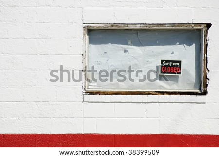 "boarded up white window of bankrupt business with ""Sorry we're closed"" sign - stock photo"
