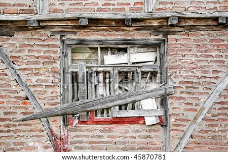 Boarded up window and grungy brick wall. Abandoned house detail
