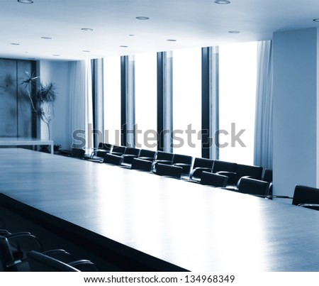 Boardroom conference room table brightly lit in blue colors - stock photo