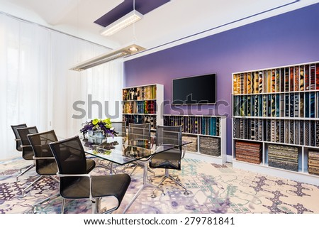 Boardroom with glass table and blue-violet walls - stock photo