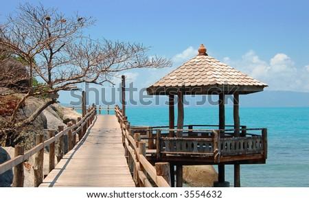 Boardwalk and Thai hut - stock photo