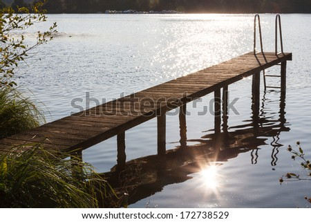 boardwalk at a lake during sundown - stock photo