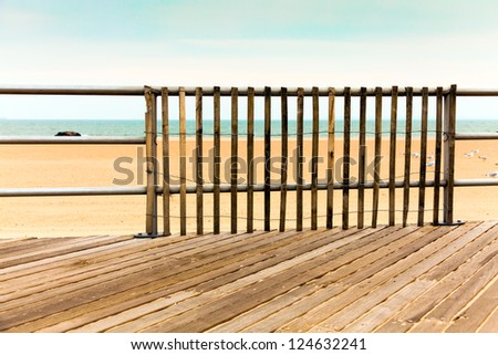 Boardwalk, empty beach and ocean.  Wooden picket railing.  Retro, vintage color palette. - stock photo