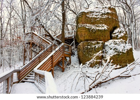 Boardwalk through a snow covered forest of northern Illinois - stock photo