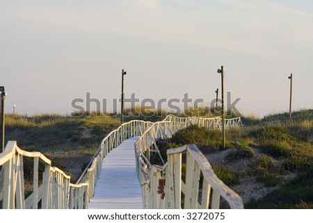 boardwalk to oceanic beach in sunset - stock photo
