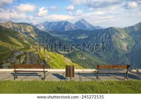 Boardwalk with empty benches in mountain - stock photo