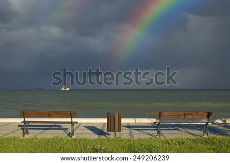 Boardwalk with empty benches on beautiful seashore against rainbow and cloudy, stormy sky - stock photo