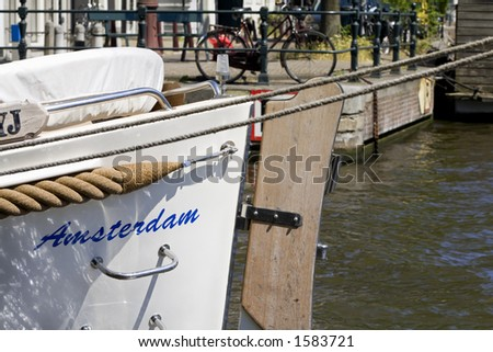 boat anchored in a canal in Amsterdam - stock photo