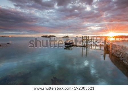 boat anchored in a harbor with a sun star - stock photo