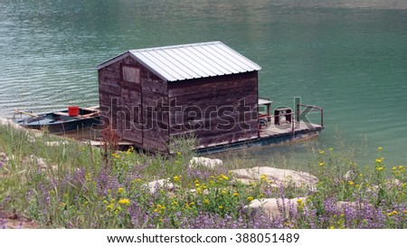 Boat and a float house on a lake near green field with yellow and purple flowers. - stock photo